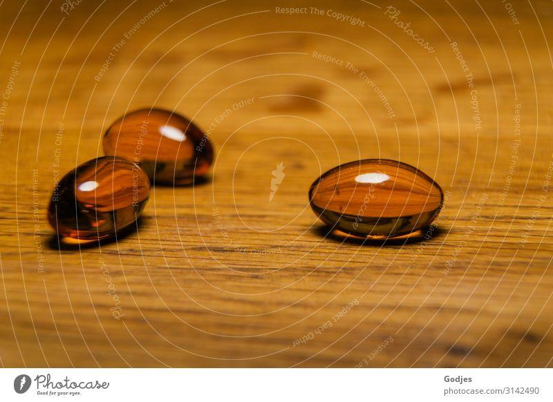 Kapseln mit Schwarzkümmelöl auf einer Holzplatte| Weltschmerz Tablette Gesundheit Zufriedenheit Allergie Krankheit Nahrungsergänzungsmittel Ernährung