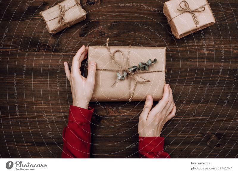 Ferienwohnung mit Frauenhänden, die eingepackte Geschenke halten. legen Aussicht Top flach Eukalyptusbaum rustikal rot neu Jahrestag Tisch Geburtstag