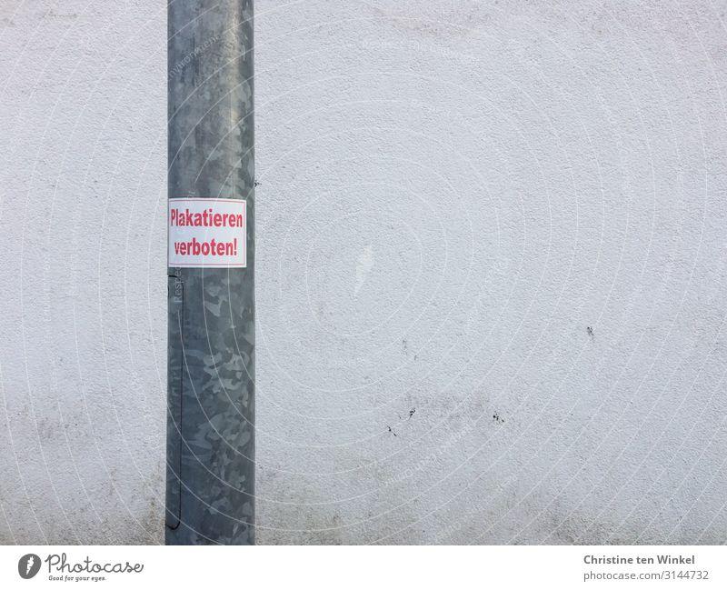 Laternenpfahl mit Aufkleber 'Plakatieren verboten' vor einer schmutzigen weißen Wand Mauer Beton Metall Schilder & Markierungen Hinweisschild Warnschild