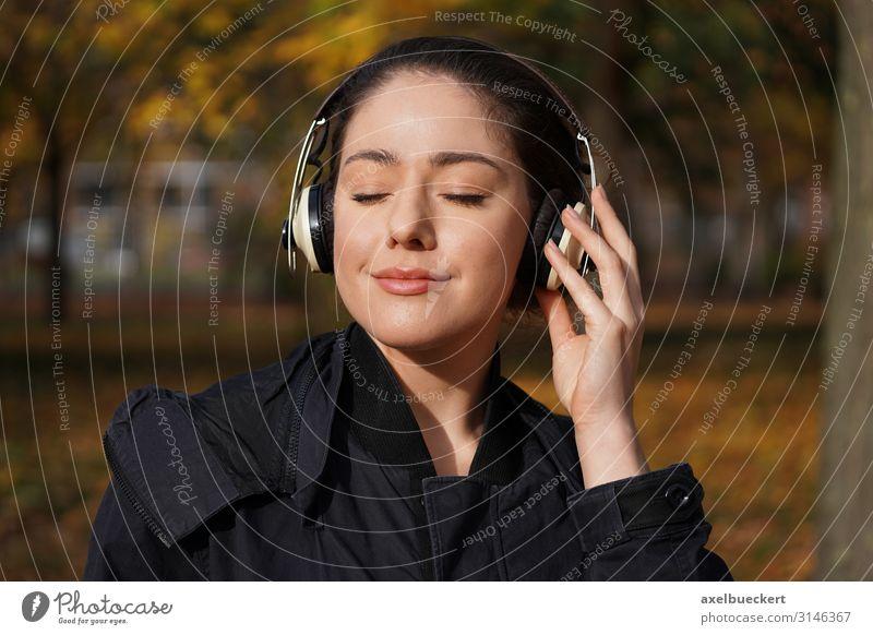 junge Frau hört draussen Musik über Kopfhörer Lifestyle Freude Freizeit & Hobby Entertainment Technik & Technologie Unterhaltungselektronik Mensch feminin