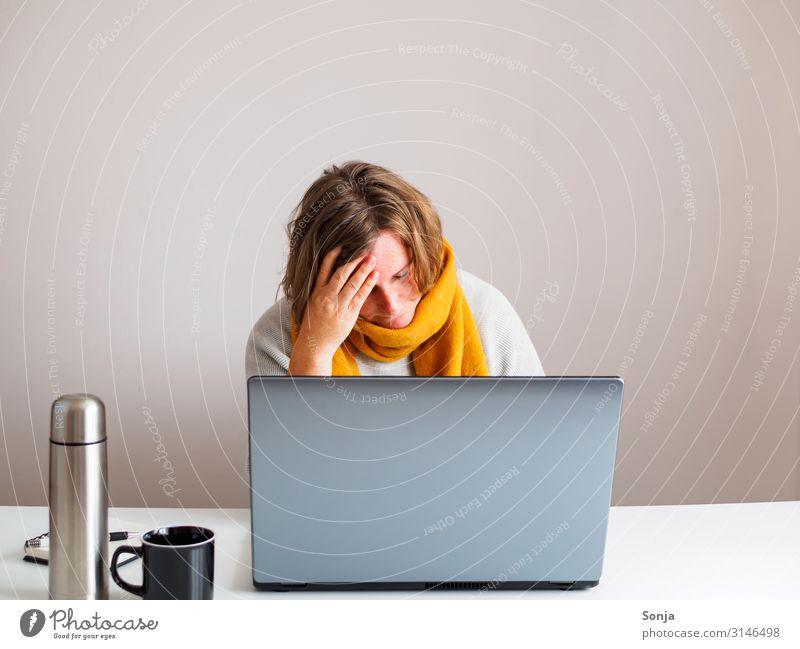 Frau mit gelben Schal und Kopfschmerzen bei der Arbeit, Grippezeit Büroarbeit feminin Erwachsene Leben 45-60 Jahre Thermoskanne Tasse Computer Stress Unlust