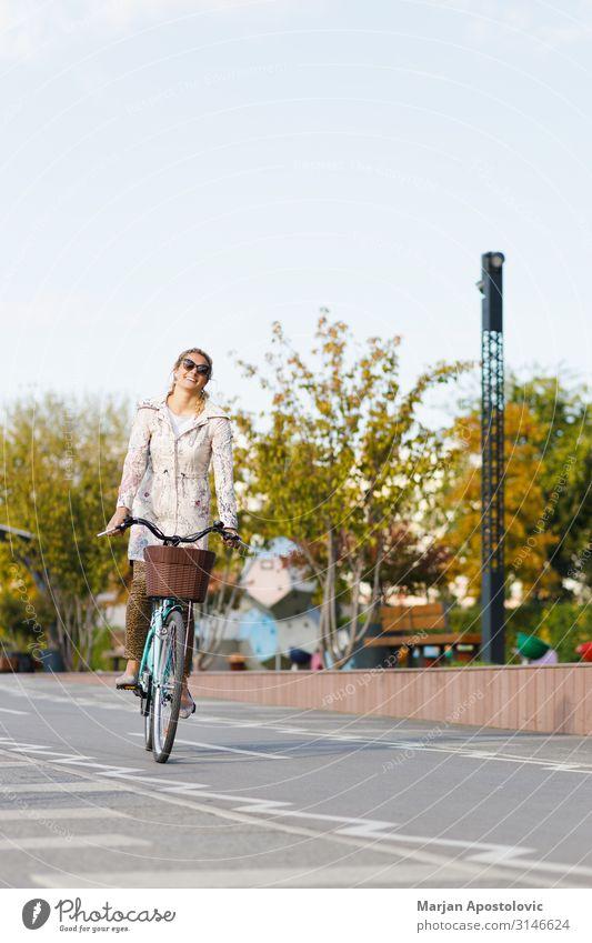 Junge Frau auf dem Fahrrad in der Stadt Freude sportlich Leben Fahrradfahren feminin Jugendliche Erwachsene 1 Mensch 30-45 Jahre Verkehr Wege & Pfade Glück
