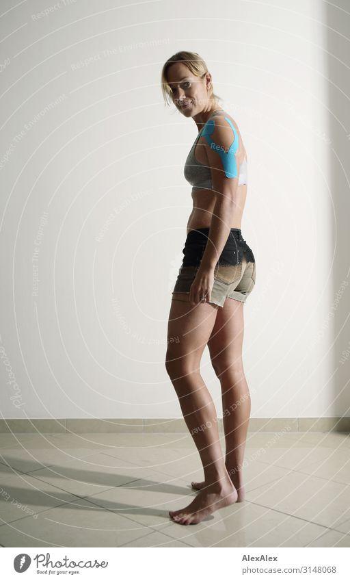 Junge Sportlerin hat Tape an der Schulter Stil schön sportlich Fitness Leben Wohnung Raum Junge Frau Jugendliche Beine 18-30 Jahre Erwachsene Hotpants Top