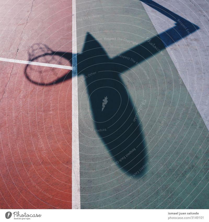 Basketballkorb Schattensilhouette auf dem roten Feld Korb Reifen Silhouette Sonnenlicht Boden Gerichtsgebäude Spielfeld Etage Sport Spielen aussetzen Straße