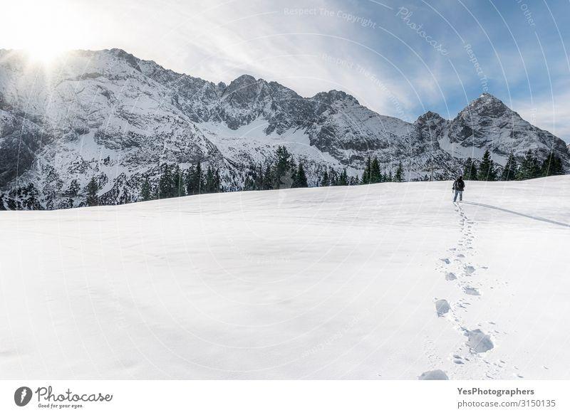 Winterberge und Mann, der durch den Schnee geht. Schritte im Schnee Abenteuer Berge u. Gebirge wandern Erwachsene 1 Mensch Natur Landschaft Sonne Klimawandel