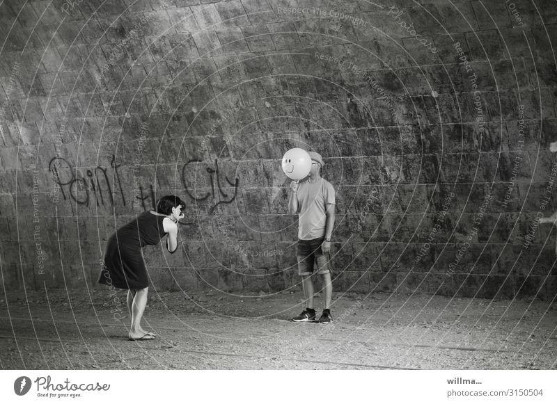 Frau fotografiert Mann mit Luftballon vor dem Gesicht - paint the city Mensch Fotograf Photo-Shooting Fotografieren lustig gesichtslos verstecken grinsen Text