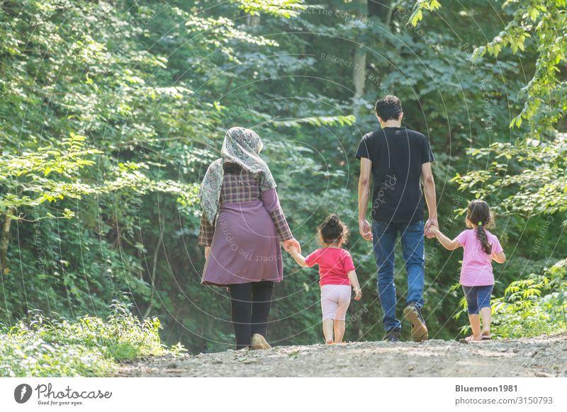 Rückseite der jungen Familie, die zusammen in grüner Natur spazieren geht. Lifestyle Erholung Ferien & Urlaub & Reisen Sommer Kindererziehung Mensch Mädchen