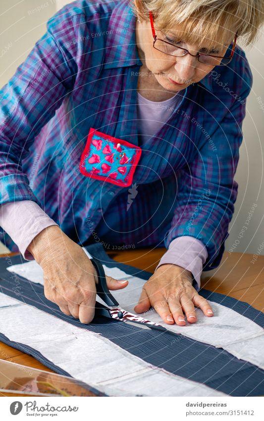 Schneiderin schneidet ein Tuch zu Design Basteln Tisch Arbeit & Erwerbstätigkeit Beruf Handwerk Schere Mensch Frau Erwachsene Mode Bekleidung Stoff alt