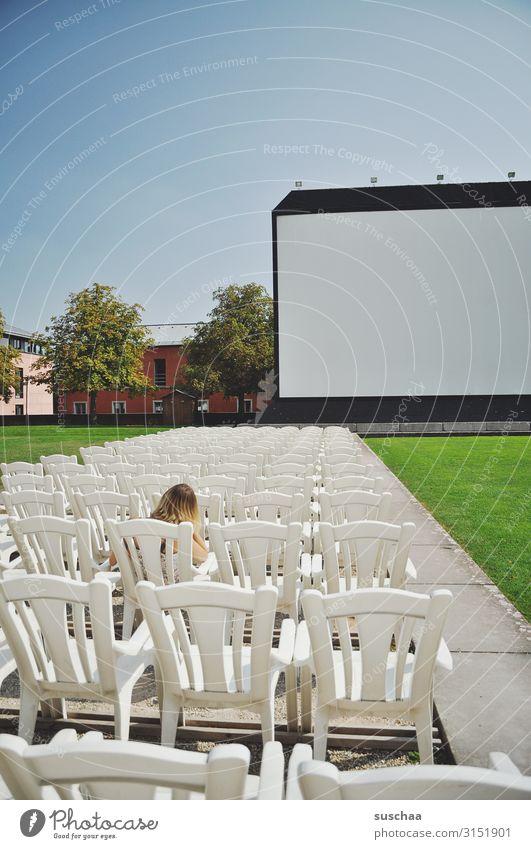teenager sitzt ganz alleine in einem open-air-kino vor einer großen leinwand Vorstellung Kino Open-Air-Kino Leinwand Platz nehmen sitzen Sitzplatz alles frei
