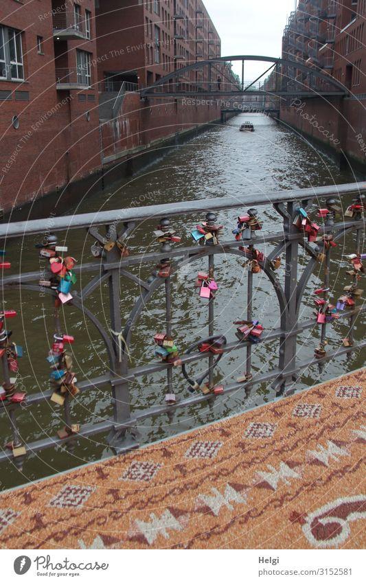 Brückengeländer mit vielen Liebesschlössern, davor ein gemusterter Teppich aus kleinen Steinen in der Speicherstadt Hamburg Wasser Hafenstadt Gebäude