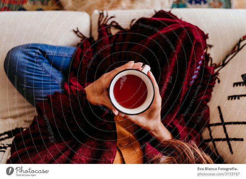 schöne Frau auf dem Sofa sitzend, eine Tasse Tee genießend. süßer Golden Retriever-Hund daneben. lebensstil im Haus. nahaufnahme heimwärts Haustier Erholung