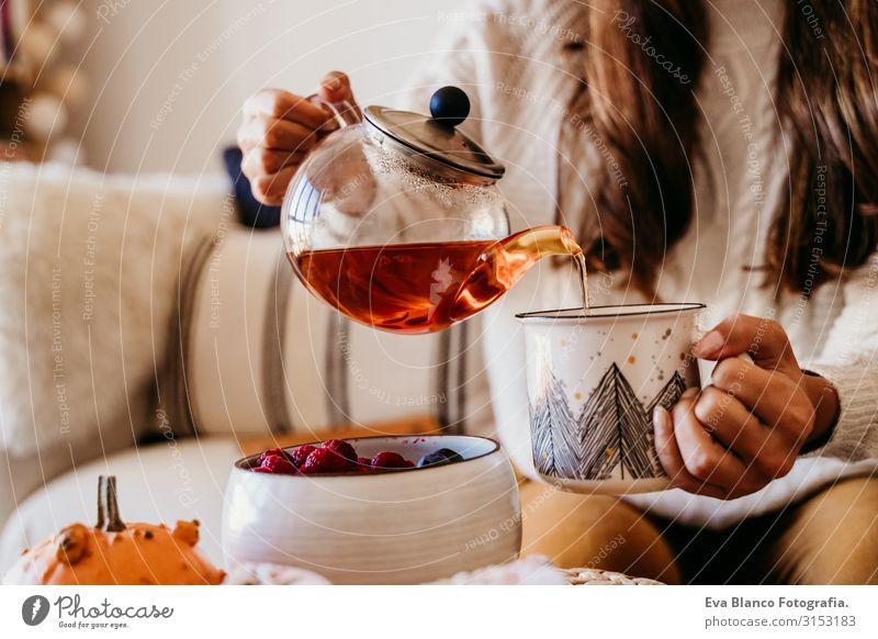 Frau, die zu Hause während des Frühstücks eine Tasse Tee trinkt. Außerdem süßer Golden Retriever-Hund. Gesundes Frühstück mit Früchten und Süßigkeiten. Leben im Haus
