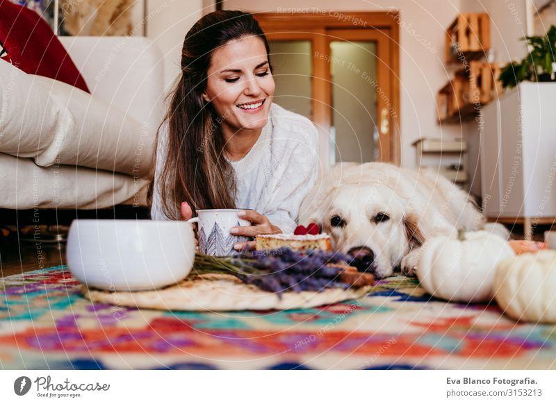 schöne Frau und süßer Golden Retriever-Hund, der zu Hause ein gesundes Frühstück genießt, auf dem Boden liegend. gesundes Frühstück mit Tee, Früchten und Süßigkeiten. Herbstzeit