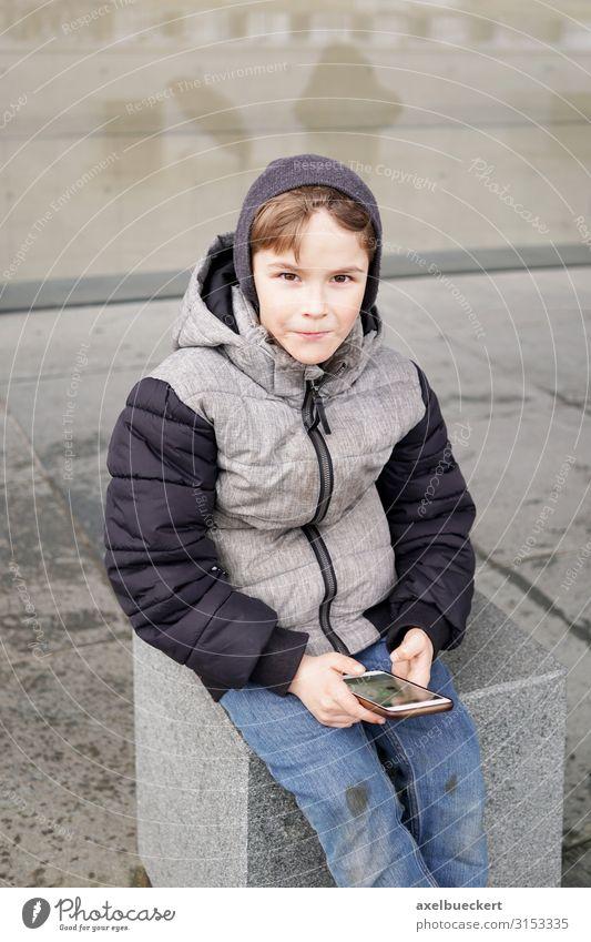 Junge mit Smartphone Kind Mensch Winter Lifestyle Spielen Schule Stadtleben Freizeit & Hobby Technik & Technologie Kindheit sitzen Telefon festhalten Internet
