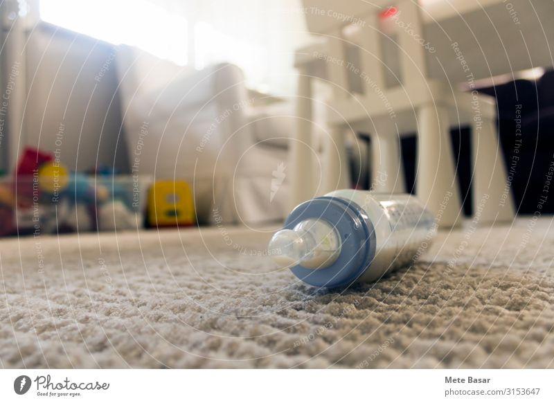 Fütterungsflasche mit etwas Milch auf einem weißen Teppich. Ernährung melken Haus Stuhl Kleinkind Spielzeug Kunststoff Tropfen Sauberkeit blau Fläschchen Tipp
