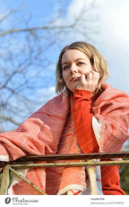 junge blonde hübsche Frau mit orangenem Pullover und Schal steht an Geländer im Freien und schaut nachdenklich in die Ferne Mensch Junge Frau Jugendliche