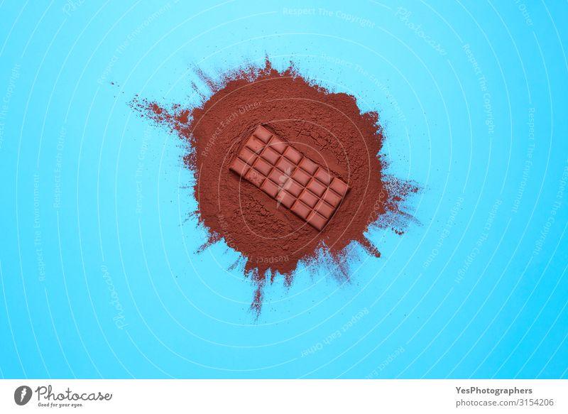 Schokoladenriegel auf Kakaopulverflor. Schokolade und Zutaten Lebensmittel Dessert Süßwaren braun Tradition Weihnachtsküche obere Ansicht Hintergrund