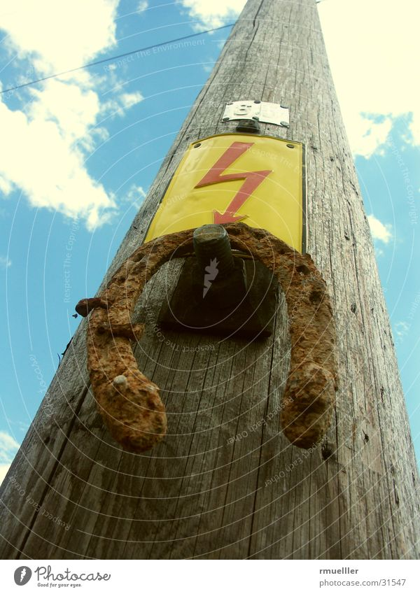 Starkstrom meets Horseshoe Himmel blau Holz braun Schilder & Markierungen Elektrizität Kabel Blitze obskur Rost Strommast Leitung Elektrisches Gerät Volksglaube