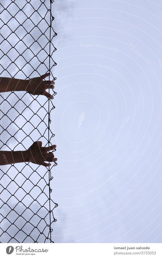 Mann, der sich einen Metallzaun schnappt. Hand Zaun Draht Geborgenheit Schutz Mensch Finger Körperteil Arme Stahl Straße Außenaufnahme packend Freiheit