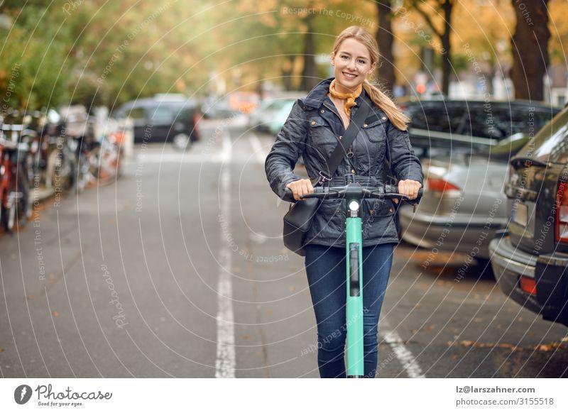 Junge glückliche Frau auf einem Elektroroller in der Stadt Lifestyle Glück Freizeit & Hobby Technik & Technologie Erwachsene 1 Mensch 18-30 Jahre Jugendliche