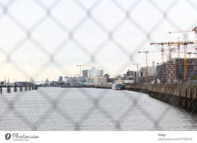 Blick durch einen Zaun auf die Elbe, Gebäude und Kräne einer Baustelle am Ufer Flussufer Hamburg Hafenstadt Bauwerk Architektur bauen stehen authentisch maritim