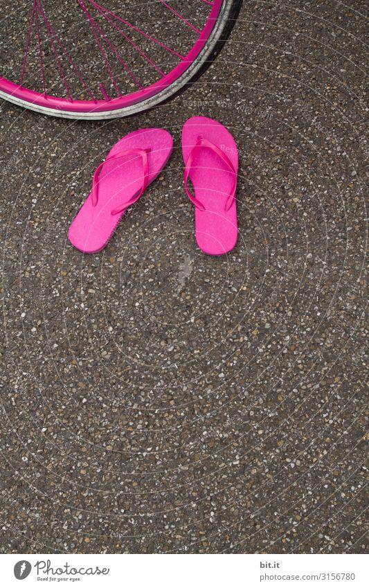 Ein Paar fnallige pinke Flip Flops, stehen herrenlos im Sommer auf dem Asphalt der Straße, vor einem Fahrradreifen in Pink und warten auf ihren Besitzer.