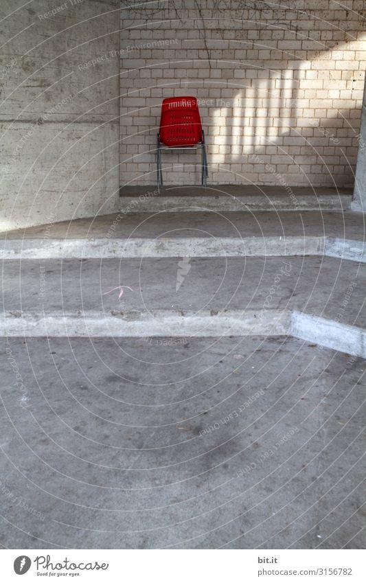 Roter Stuhl aus Plastik, mit Lichteinfall vor Mauer. Bauwerk Gebäude Architektur Wand Treppe Fassade Stein Beton Linie Pfeil Streifen sitzen Sonnenlicht einzeln