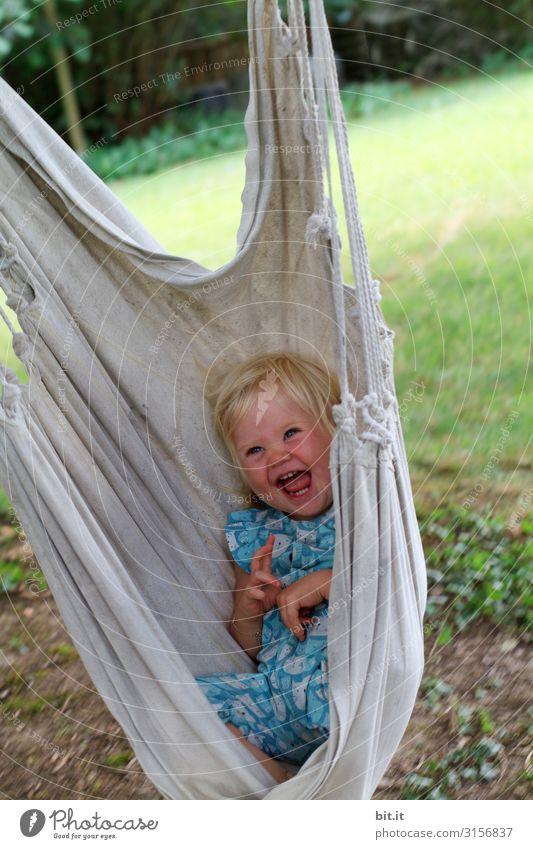 Kleines, süßes, blondes Mädchen sitzt, liegt glücklich und strahlend in einer Hängematte für Kinder im Garten und lacht herzhaft in die Kamera. Freizeit & Hobby