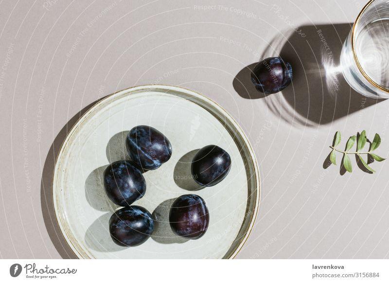 Minimalistische Flachlegung von Pflaumen auf einem handgefertigten Teller und Wasser Ast lecker Dessert Diät Essen Lebensmittel Gesunde Ernährung frisch Frucht