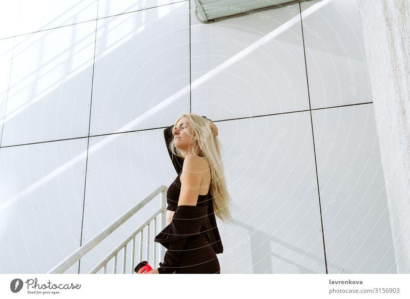 Junge erwachsene blonde Frau in Sportkleidung, die sich nach dem Training ausruht Einsamkeit attraktiv Körper Kaukasier Großstadt Fitness Behaarung Glück
