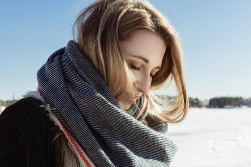 Nahaufnahme eines weißen Mädchens in einem Schal auf einem gefrorenen Fluss. Herbst blond Kaukasier Mantel kalt Gesicht Junge Frau Behaarung Lifestyle Natur