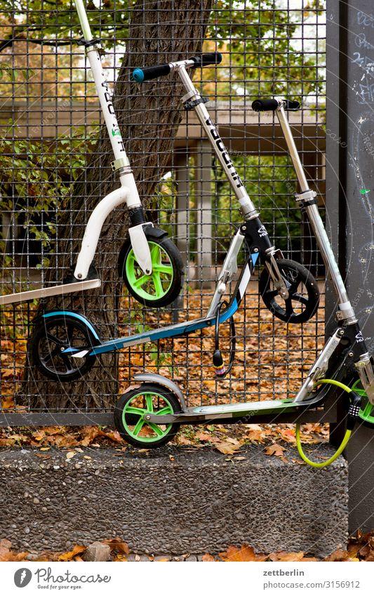 Drei Roller Parkplatz Erholung aufbewahren Grenze Herbst hängen Kindergarten Maschendrahtzaun Menschenleer parken Tretroller Schulgebäude Schulhof Textfreiraum
