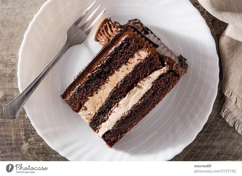 Schokoladenkuchenscheibe auf Holztisch Backwaren Kuchen Scheibe süß Dessert Pasteten Lebensmittel Foodfotografie gebastelt Sahne Torte Pudding backen
