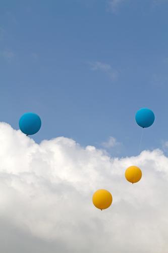 Vier Luftballons in Gelb und Blau an einer Schnur, fliegen draussen bei einem Fest nach oben in die Luft, in den blauen Himmel mit Wolken l 1600 Freiheit Party