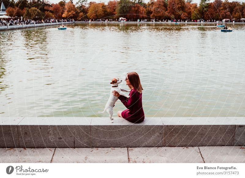 junge Frau und süßer Hund am See in einem städtischen Park. Konzept der Liebe zu Tieren. Retiro-Park Madrid Haustier Außenaufnahme Großstadt Umarmen