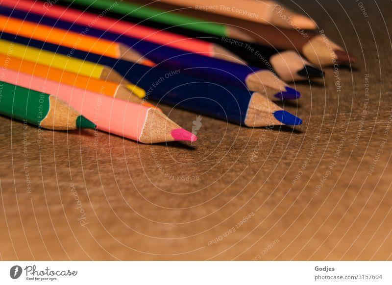 Farbige Buntstifte liegend auf braunem Untergrund | Firlefanz Schreibwaren Zettel Farbstift Schreibstift zeichnen blau mehrfarbig gelb grün violett orange rosa