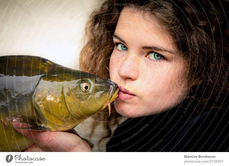 Junge Frau mit eindrucksvollen grünen Augen, die einen Karpfen, Fisch und andere Tiere küssen. Meeresfrüchte Abendessen Lifestyle Glück schön Gesicht Angeln