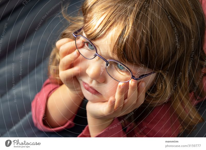 Junges blauäugiges Mädchen mit Brille, das ins Licht schaut. schön Kind Baby Kindheit Auge blond Denken klein niedlich Konzentration unschuldig jung Tochter