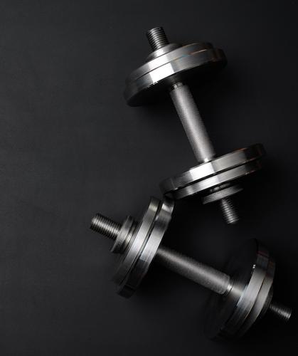 Paar glänzende Stahlsetzhanteln für Bodybuilding Lifestyle sportlich Sport Werkzeug Metall Fitness stark grau schwarz Kraft Entwurf Hintergrund Chrom Kurzhantel