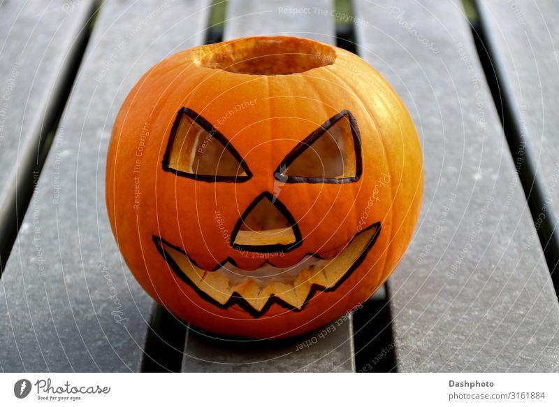 Geschnitzter Halloween-Kürbis auf einer eisigen Picknickbank Lebensmittel Gemüse Frucht Gesicht Freizeit & Hobby Dekoration & Verzierung Feste & Feiern Herbst