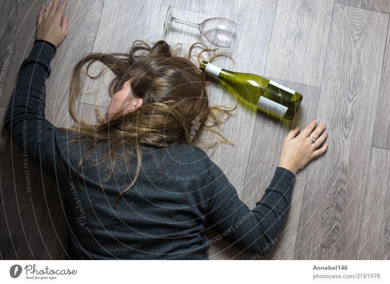 Betrunkenes alkoholisches junges Mädchen, das auf dem Boden liegt und sich krank fühlt, weil es Rotwein, ein leeres Glas und eine Flasche Knock-out getrunken hat