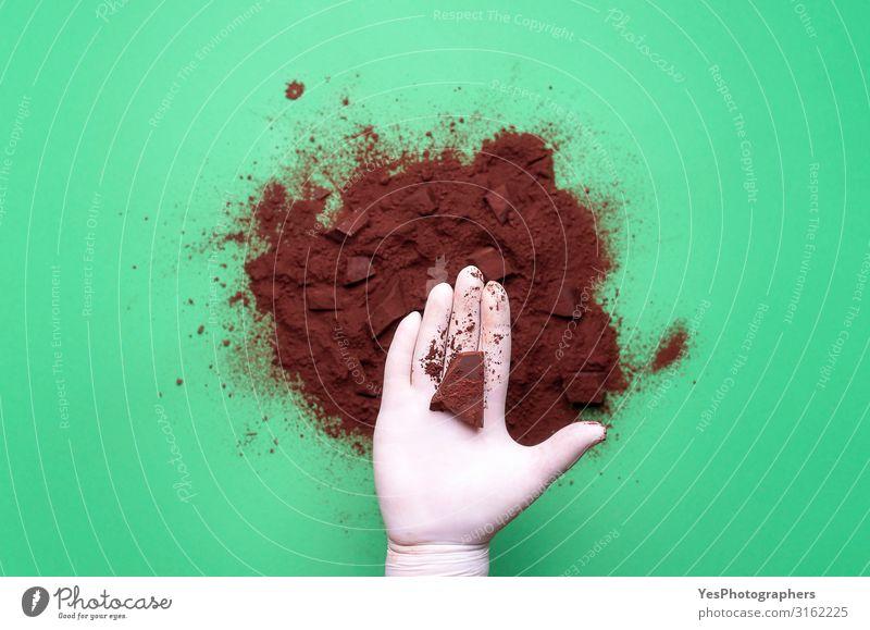 Schokoladenstück in der Hand und Kakaostapel Schokoladenstück und Kakao Dessert Süßwaren braun Tradition obere Ansicht Hintergrund Kakaopulver