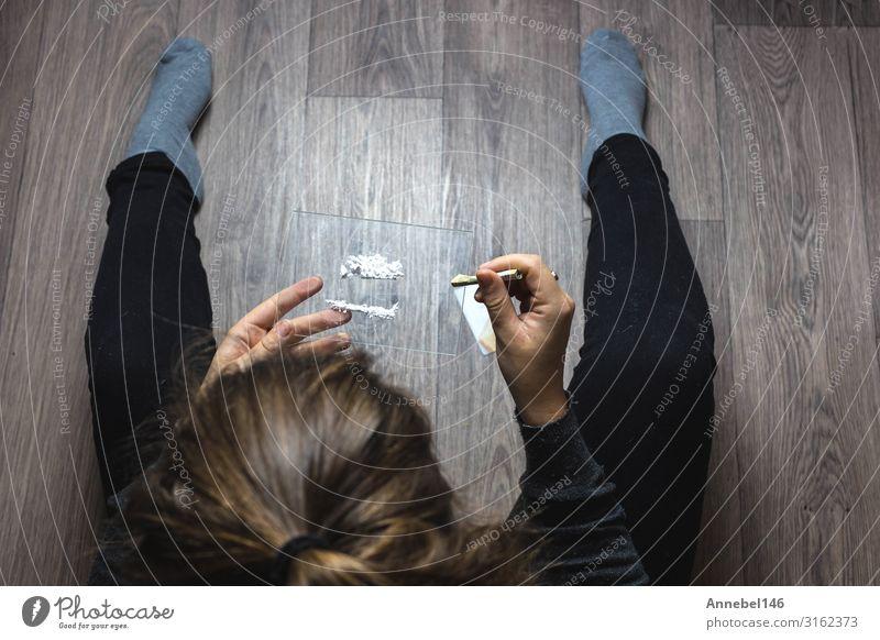 Junge Frau, die Drogen, Kokain oder Geschwindigkeit oder andere Drogen schnaubt. Geld Tisch Erwachsene Jugendliche Hand Linie Traurigkeit schwarz weiß