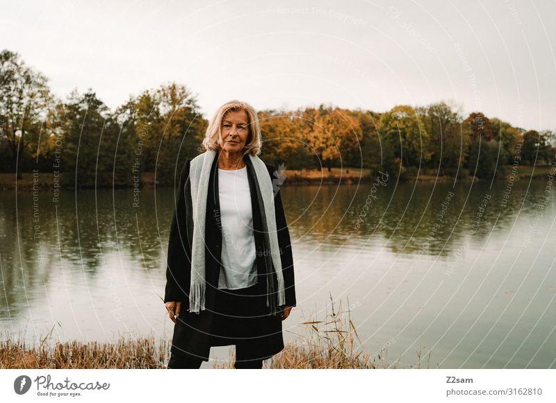 TRAUDL Lifestyle elegant Stil Frau Erwachsene Weiblicher Senior 45-60 Jahre Natur Landschaft Herbst Schönes Wetter See Mode Mantel Schal blond Blick Coolness