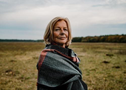60 jährige Dame mit Schal in Herbstlandschaft Stil Weiblicher Senior Frau 60 und älter Natur Landschaft Wolken Wiese Mantel Tuch blond Blick elegant Gesundheit