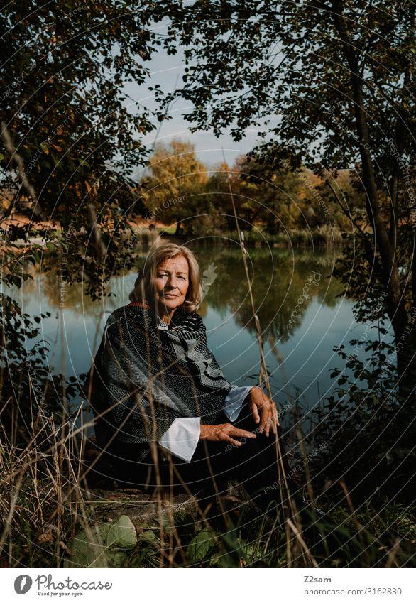 Herbstportrait Lifestyle Frau Erwachsene Weiblicher Senior 45-60 Jahre 60 und älter Natur Landschaft Schönes Wetter Sträucher Wald Seeufer Jacke Schal blond