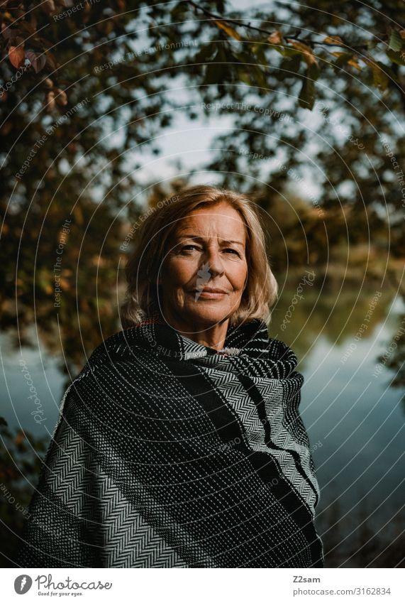 TRAUDL Lifestyle elegant Stil Frau Erwachsene Weiblicher Senior 45-60 Jahre 60 und älter Natur Landschaft Herbst Schönes Wetter Baum Sträucher Seeufer Umhang