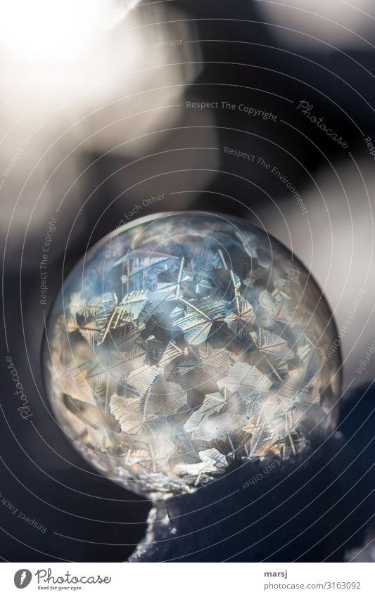 Gefrorene Seifenblase liegt am Abgrund. Da sie weich gebettet im Schnee liegt kann sie nicht runterrollen. Vergänglichkeit Reinheit bizarr kalt gigantisch
