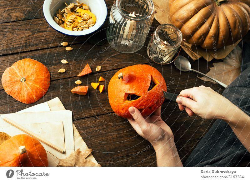 Ein Mann macht ein Gesicht aus einem Kürbis. Halloween orange heimwärts jack-o-lantern Tradition Feiertag Herbst Oktober traditionell selbstgemacht Laterne
