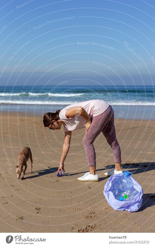 Frau mit Hund, die Müll und Plastik aufhebt und den Strand reinigt. Flasche Lifestyle Meer Mensch feminin Erwachsene Hand 30-45 Jahre Umwelt Natur Landschaft